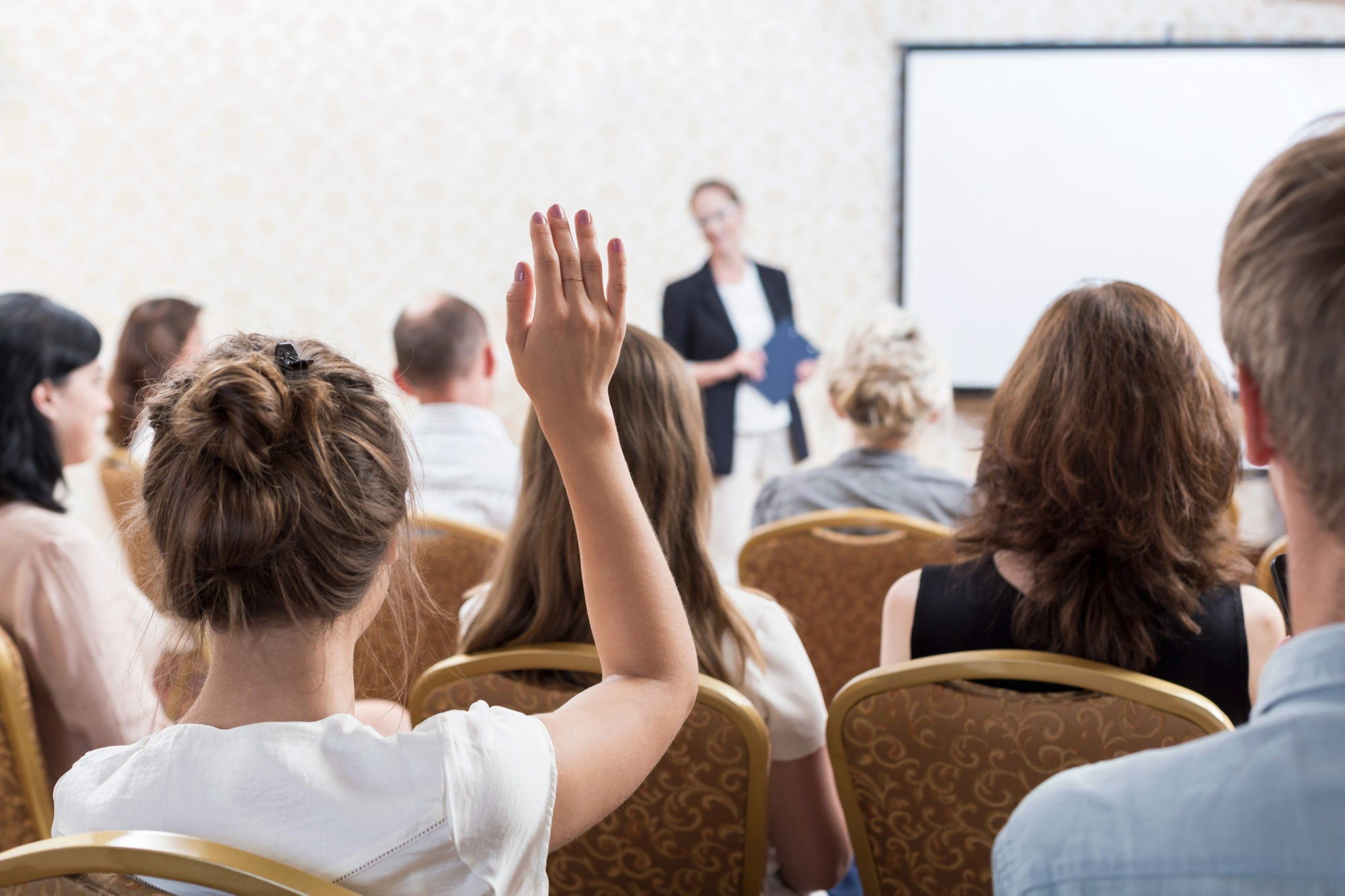Photo of listener raising hand to ask question during seminar