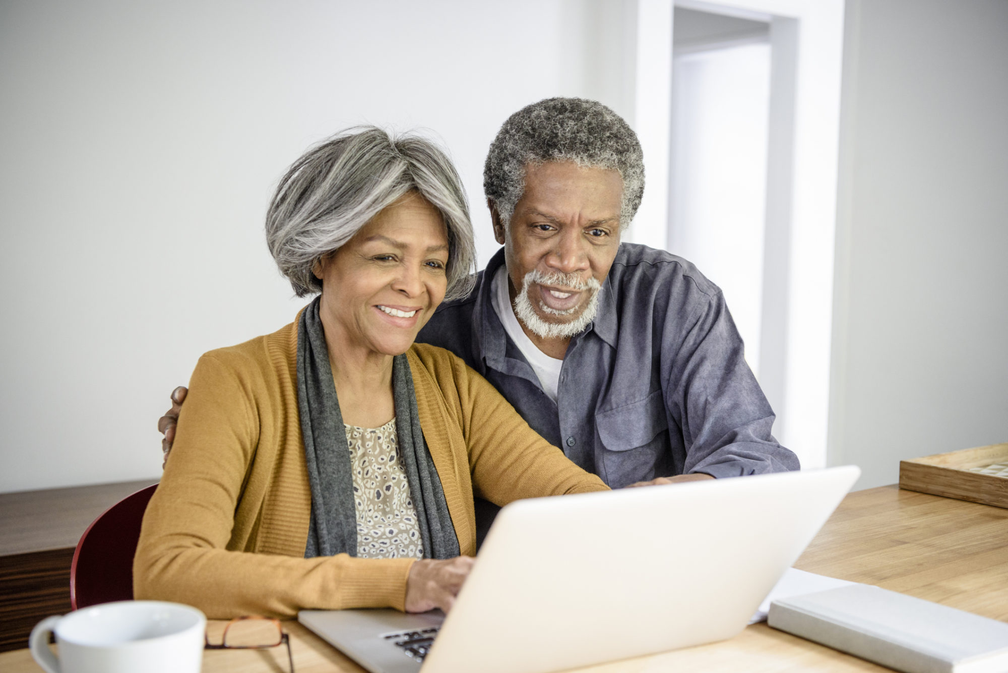 Senior African American couple using laptop together at home. The woman is typing and the man is watching her with his arm around her